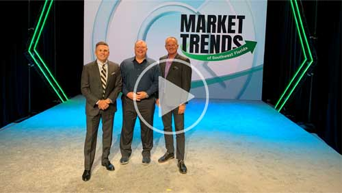 3 men in suits smiling on stage with Market Trends Logo behind them